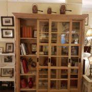 Libreria in abete vecchio con tre ante scorrevoli, finitura naturale. Particolare dell'apertura. Mobili country su misura Siena e Firenze