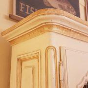 Libreria provenzale tre sportelli in legno di noce laccata a mano. Particolare del cappello. Mobili country su misura Siena e Firenze.