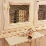 Libreria provenzale tre sportelli in legno di noce laccata a mano. Particolare della mensola estraibile. Mobili country su misura Siena e Firenze.