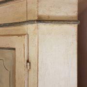 Angoliera in legno di tiglio a un'anta decorata e laccata a tempera nei colori bianco e azzurro. Particolare cappello. Arredamento contemporaneo su misura Siena e Firenze