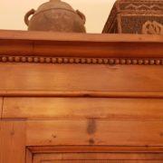 Armadio toscano due ante in legno di abete, metà Ottocento. Particolare della decorazione sotto il cappello. Mobili antichi Siena e Firenze