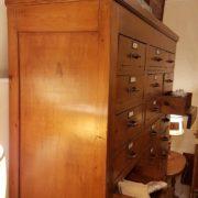 Cassettiera schedario originale primi del Novecento in legno di abete a trenta cassetti con fronte ribaltabile. Il fianco. Mobili antichi Siena e Firenze