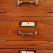 Cassettiera schedario originale primi del Novecento in legno di abete a trenta cassetti con fronte ribaltabile. Particolare. Mobili antichi Siena e Firenze