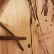 Orologio da muro rotondo country in legno di pino spazzolato decapato con numeri romani e cornice in ferro finitura ruggine. Finitura. Mobili country Siena e Firenze