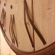 Orologio da muro rotondo country in legno di pino spazzolato decapato con numeri romani e cornice in ferro ruggine. Particolare. Mobili country Siena e Firenze