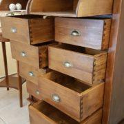 Cassettiera schedario in legno di tiglio massello a sedici cassetti, di cui otto superiori ribaltabili. Particolare aperto. Arredamento classico contemporaneo