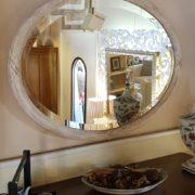 Specchiera ovale in legno con intaglio in finitura laccata decapata.Frontale.Mobili country Siena e Firenze