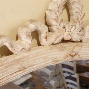 Specchiera ovale in legno con intaglio in finitura laccata decapata.Particolare intaglio.Mobili country Siena e Firenze