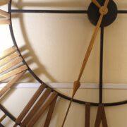 Orologio in ferro anticato con lancette e numeri romani in foglia oro. Particolare centrale. Arredamento classico contemporaneo Siena e Firenze